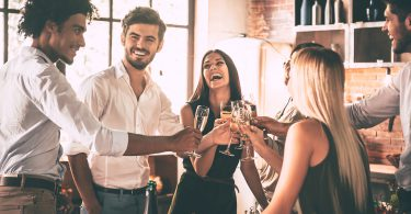 Meeting with old friends. Cheerful young people cheering with champagne flutes and looking happy while having home party