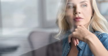 Dreaming of happiness. Close up portrait of pretty young blond woman intently looking aside near window.