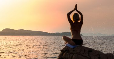 Silhouette young woman practicing yoga on the beach at sunset. Muscle tone.