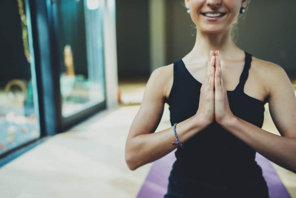 Mulher sorrindo com as mãos juntas em posição de namastê.