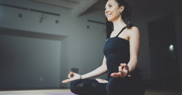 Portrait of happy young woman practicing yoga indoor. Beautiful girl practice lotus position in class.Calmness and relax, female happiness.Horizontal, blurred background, flares