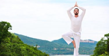 Man Doing Indian classic art Yoga at the Sea and Mountains