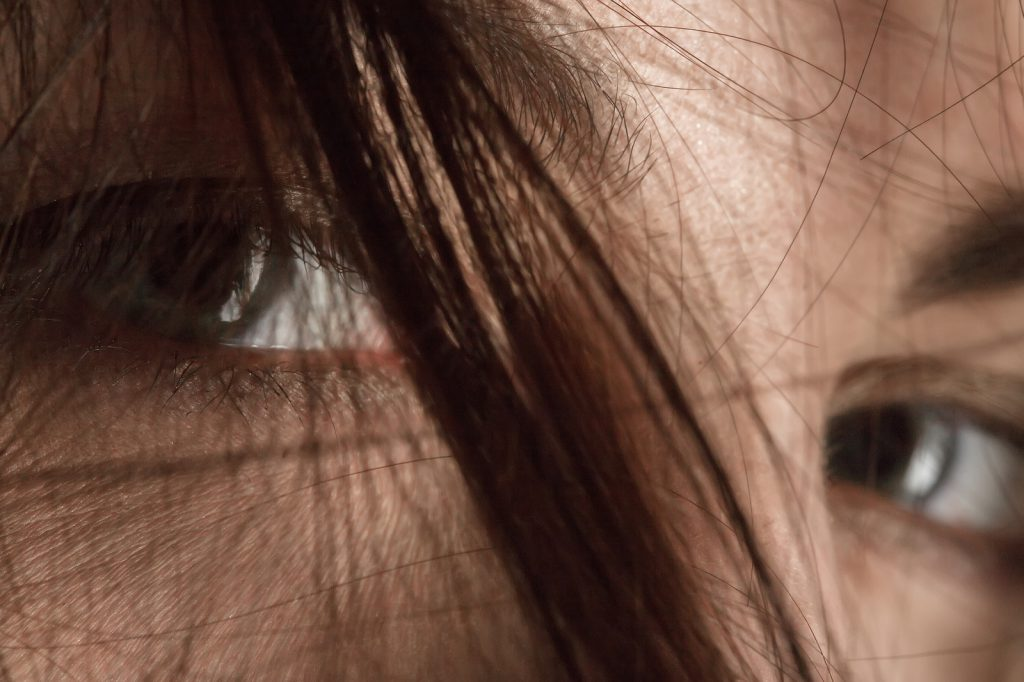 sad female eyes under blowing hair close up macro image
