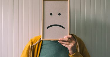 Put a sad pessimistic face on sadness and depressive emotions concept man holding picture frame with smiley emoticon printed
