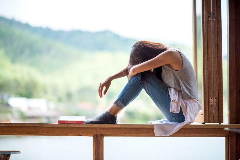 Jovem mulher atraente sentada em uma janela com humor solitário