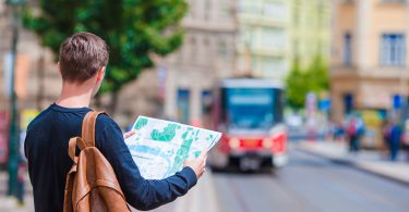Happy young man with a city map and a backpack smiling