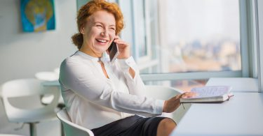 Happy smiling businesswoman looking at window while talking over mobile or smart phone with friends or closed relatives. Business rest concept. Break concept.