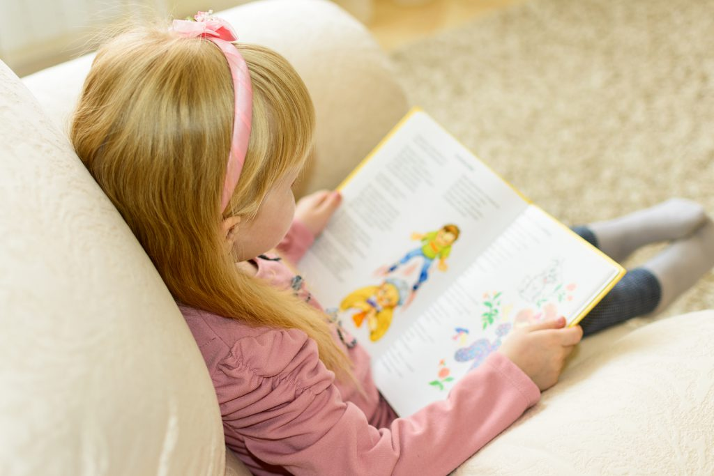 a girl reading a book sitting in a chair