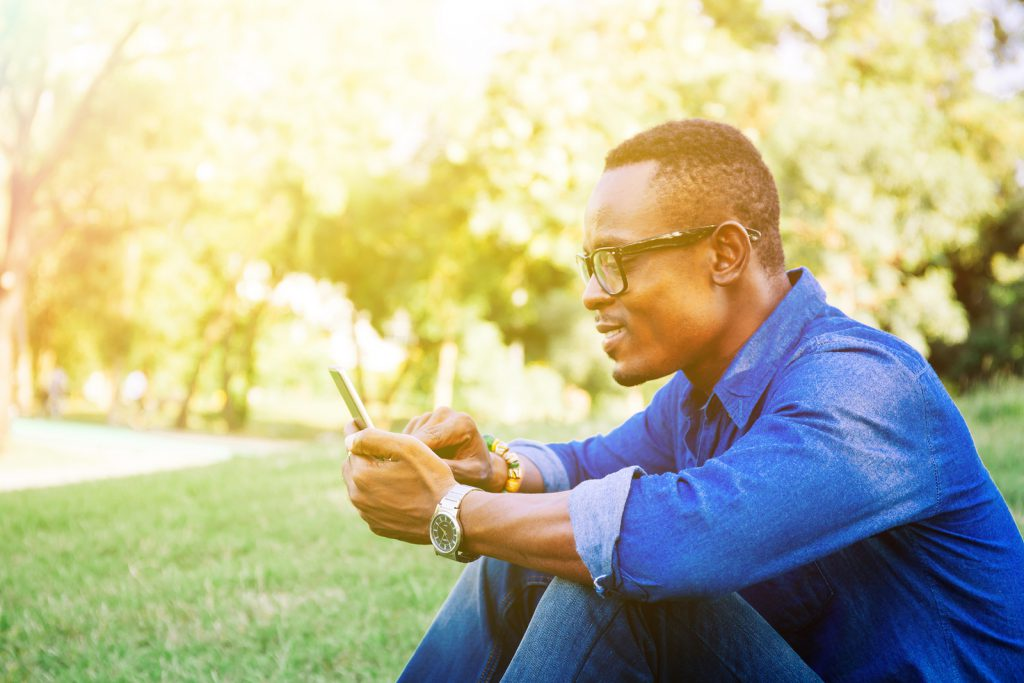 African American man using mobile phone in the park