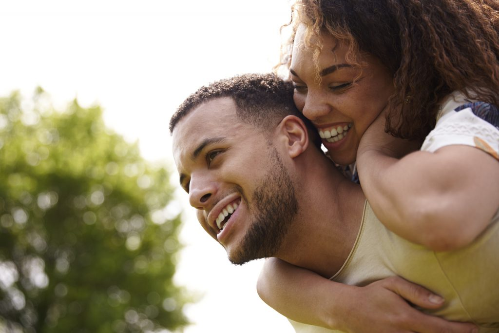 Close up of young adult couple piggybacking outdoors, side view