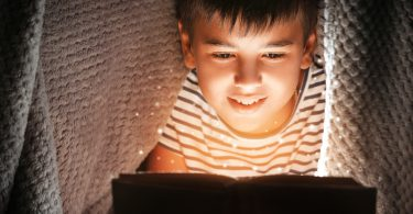 Cute boy reading book under blanket at night. Magic light coming out of book.