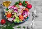 Healthy vegetarian food fresh vegetables salad with different vegetables radishes cherry tomatoes lettuce salad dill sauce olive oil fresh whole radishes blue plate on light wooden background
