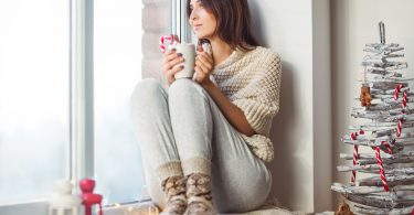 Happy beautiful woman drinking hot coffee sitting on window sill in christmas decorated home. Holiday concept