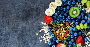 Fresh healthy ingredients (oat flakes green grapes banana berries with yogurt and seeds) for breakfast or smoothie on dark vintage background - Healthy food Diet Detox Clean Eating or Vegetarian concept.