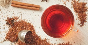 Rooibos traditional organic dieting drink. Healthy superfood beverage rooibos african tea with spices on vintage wooden background