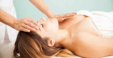 Beautiful young Hispanic woman getting positive vibes during a reiki session at a health clinic and spa