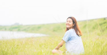 Young woman sitting at relax pose or freedom pose or chill pose on the meadow during sunrise at morning. Riverside.