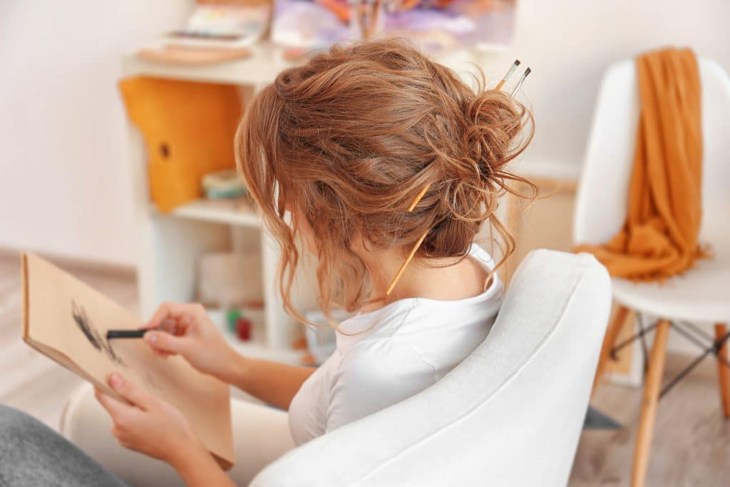 Young female artist drawing sketch in studio