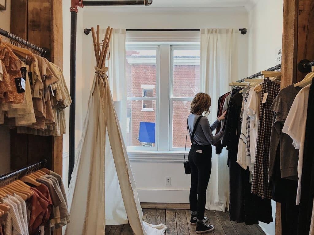 Mulher procurando uma peça em um armário de roupas.