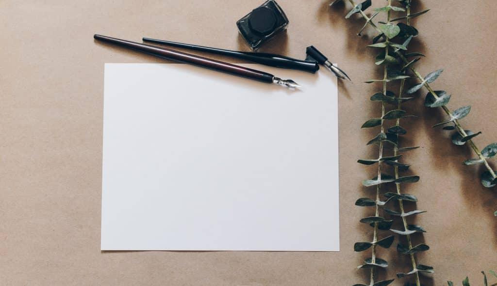 Papel na mesa com caneta ao lado de alguns ramos de folhas