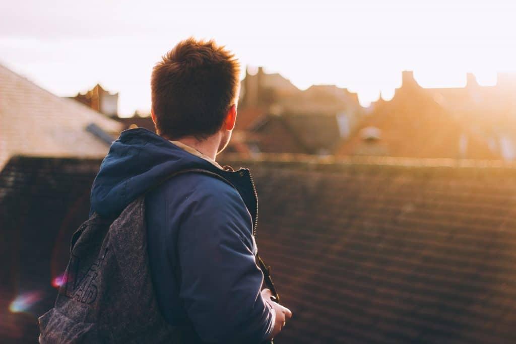 Homem de costas em uma cidade com o céu de entardecer.