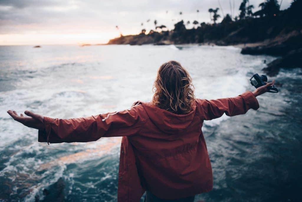 Mulher em frente ao mar com os braços abertos.