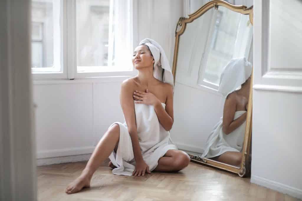 Mulher enrolada em uma toalha de banho, sentada no chão, sorrindo em frente ao espelho.
