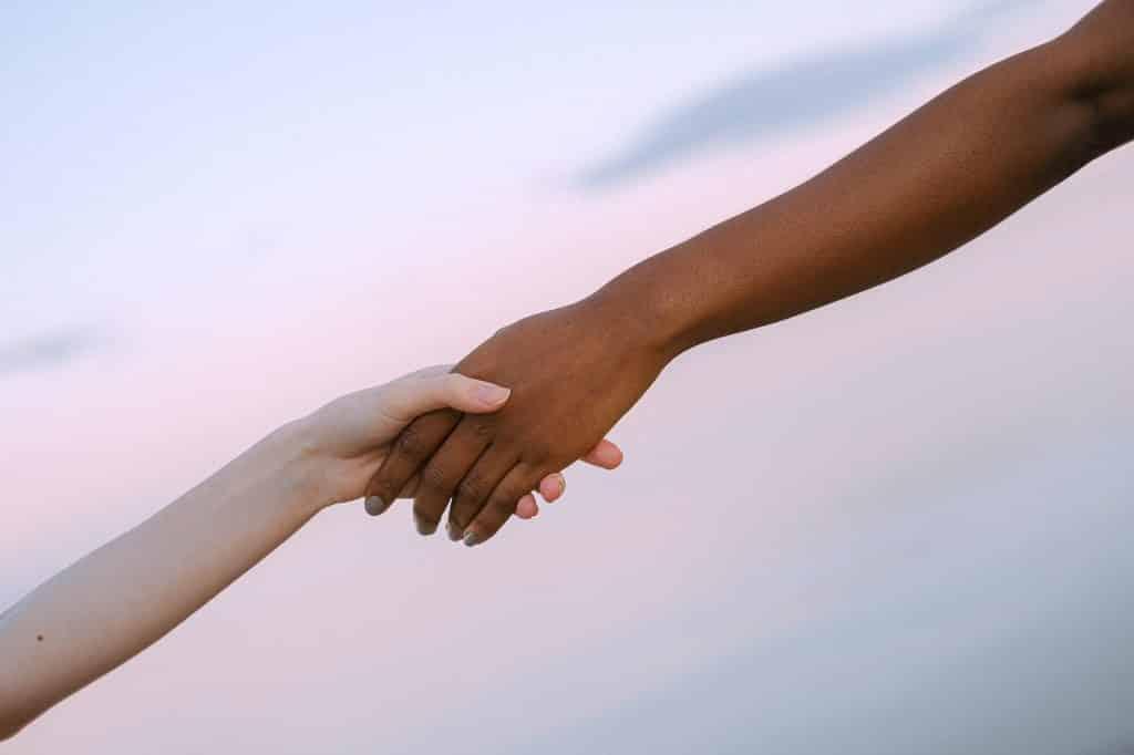 Duas mãos entrelaçadas em frente ao céu ao fim da tarde.