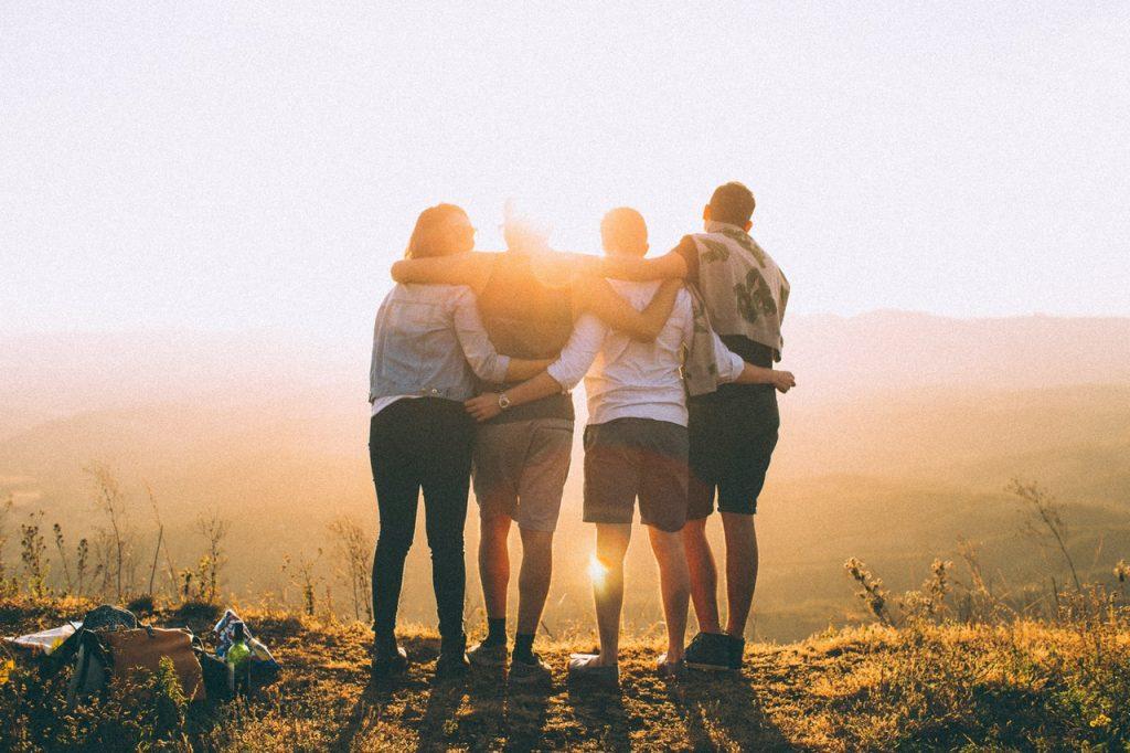 Amigos abraçados lado a lado, vistos de costas admirando uma paisagem natural, ao pôr do sol.