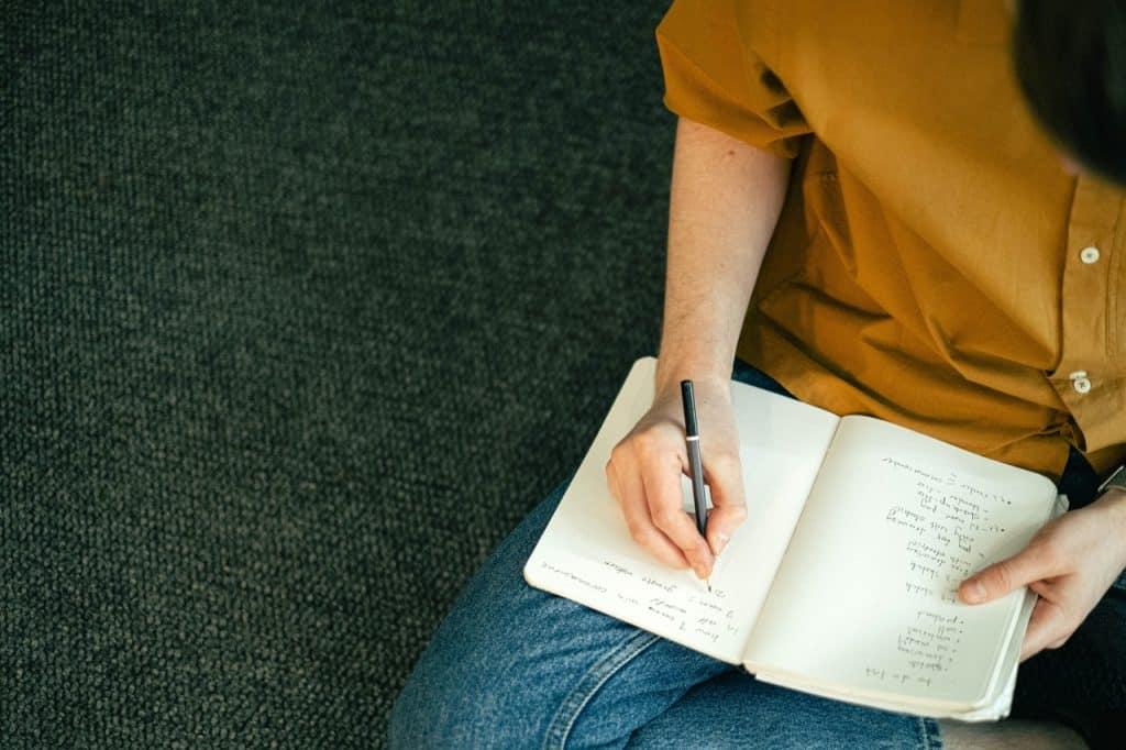 Pessoa sentada no chão, escrevendo em um caderno no seu colo.