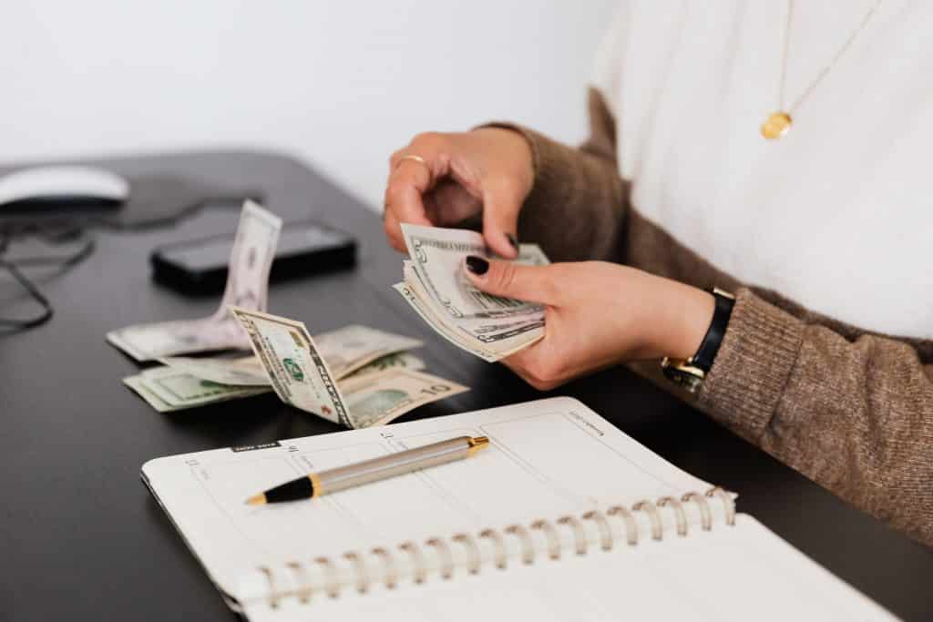 Mulher cotando dinheiro ao lado de uma agenda