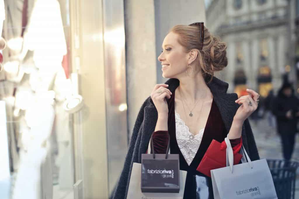 Mulher carregando sacolas de compras olhando pela vitrine de uma loja.