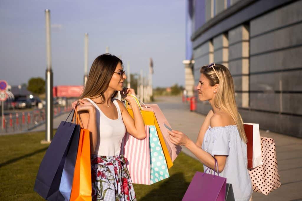Duas mulheres conversando enquanto seguram sacolas de compras.