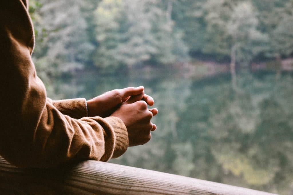 Mãos apoiadas em uma ponte. À frente está um lago envolto por árvores.