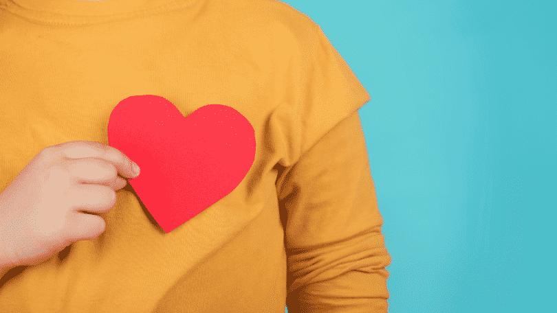 Pessoa segurando um coração vermelho na frente do peito