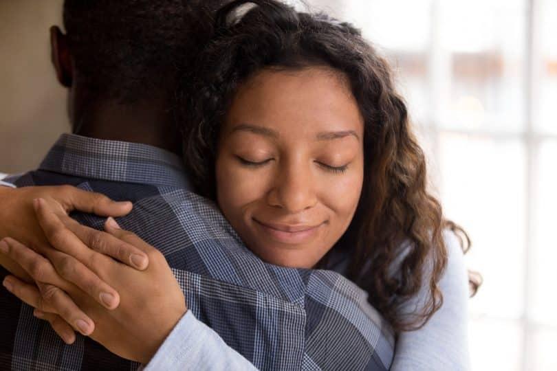 Mulher negra abraçando homem negro com expressão relaxada