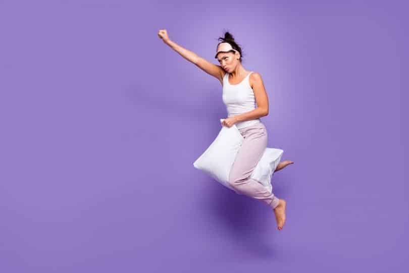 Mulher com travesseiro sobre as pernas em cenário roxo. Ela flutua e ergue um braço, enquanto o outro segura o travesseiro. Seu semblante é de determinação.