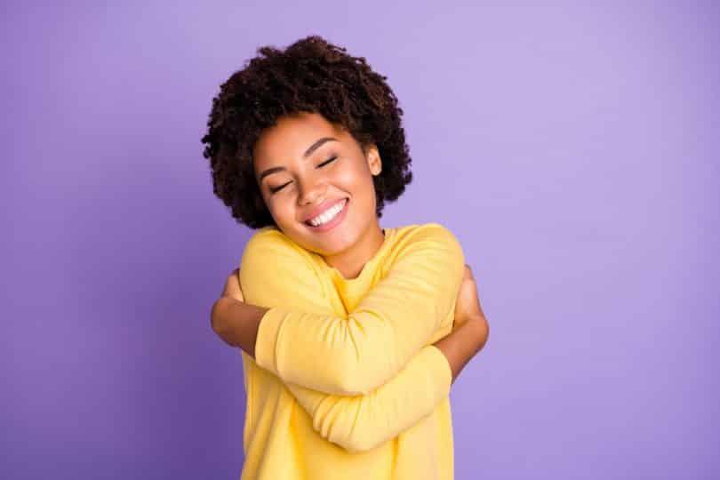 Foto de uma jovem se abraçando e sorrindo em um fundo roxo.
