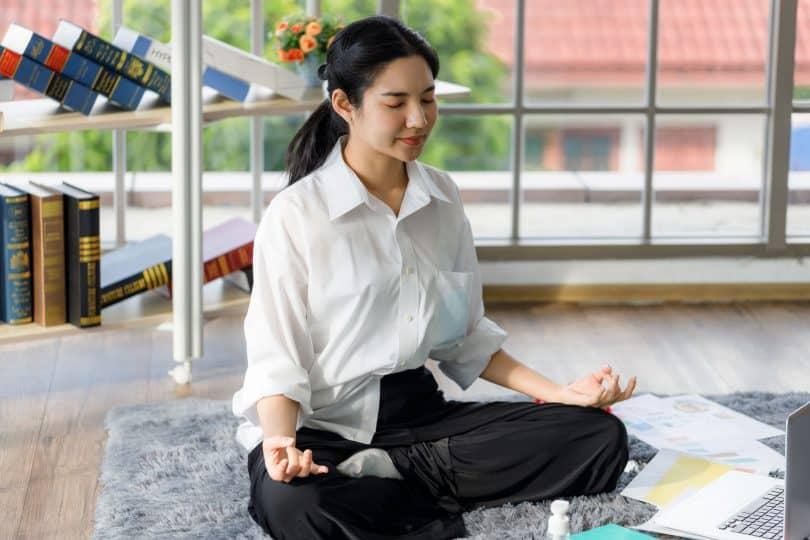 Garota chinesa meditando na sala de casa.