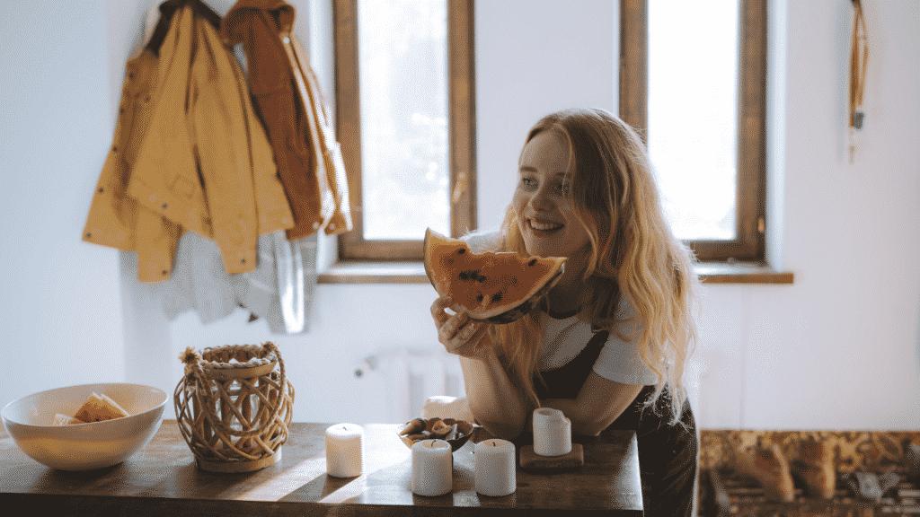 Garota contente comendo melancia