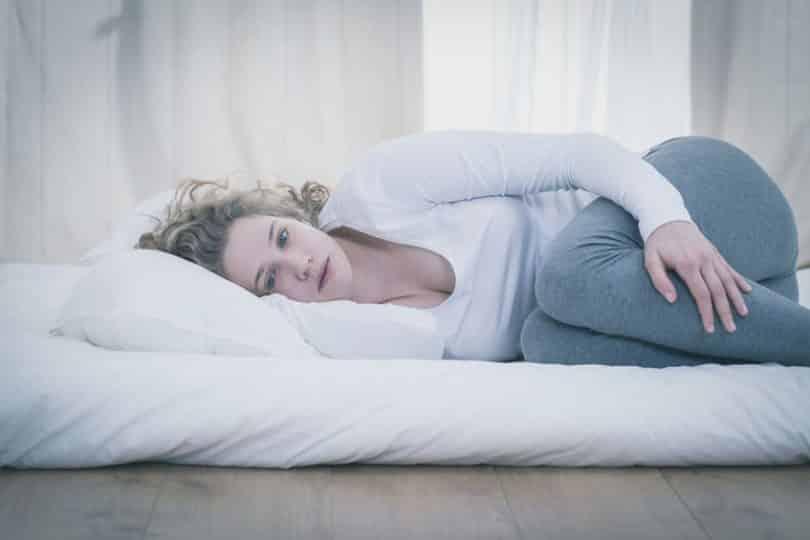 Mulher deitada em colchão com travesseiro e expressão triste