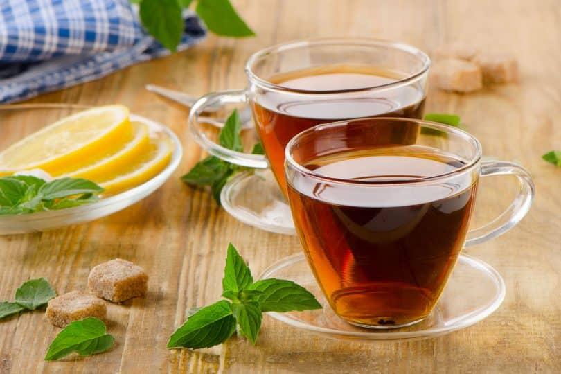 Xícaras de chá de vidro com hortelã e limão em uma mesa de madeira.