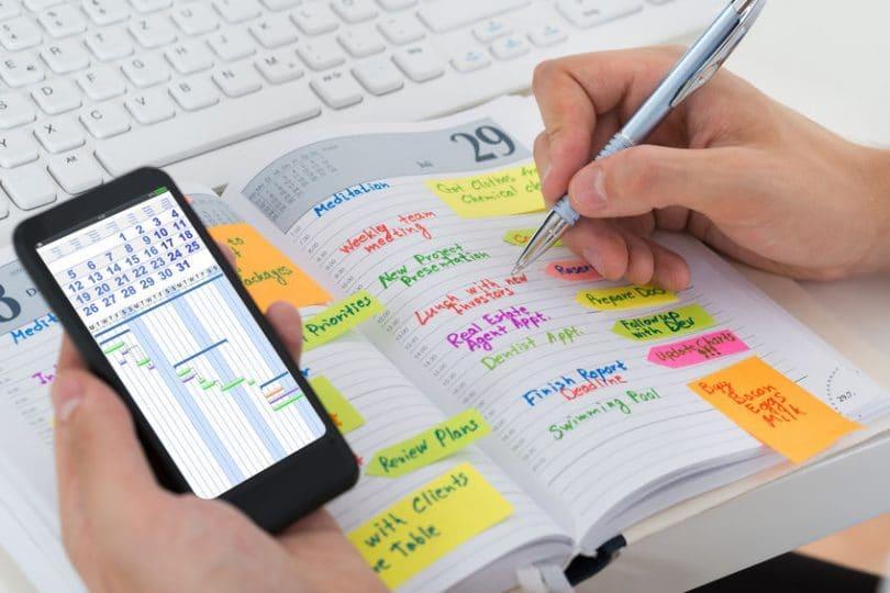 Pessoa segurando celular exibindo gráficos, com a mão esquerda, e escrevendo em uma agenda cheia de anotações coloridas, com a mão direita.