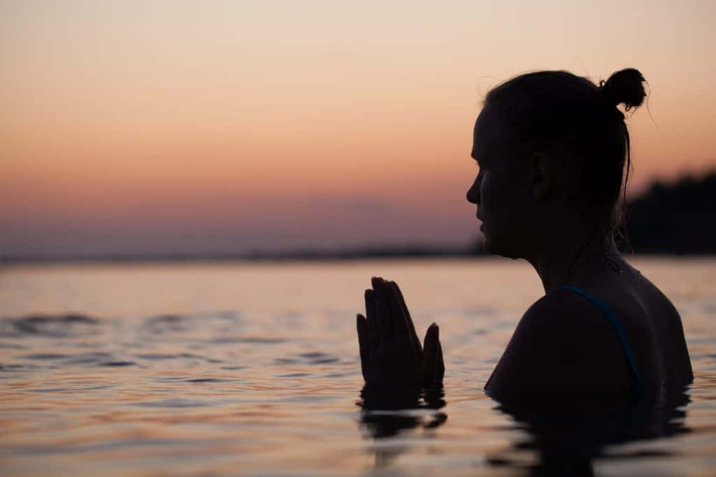 Woman in sea water at sunset alone. She praying or meditating
