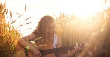 Beautiful young girl playing guitar in the golden wheat field. Lens flare selective focus toned image.
