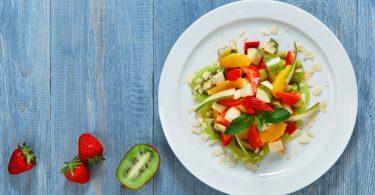Vegan food. Vegetarian diet. Fruit salad at white plate. Fruit salad closeup. Healthy diet food, natural organic vegan salad with pear, strawberry, orange and almond slices.