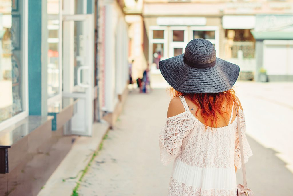 Rear view of a girl with red hair in a black hat walking around the city. Sunny summer day. City style.Girl wearing stylish summer dress of lace.