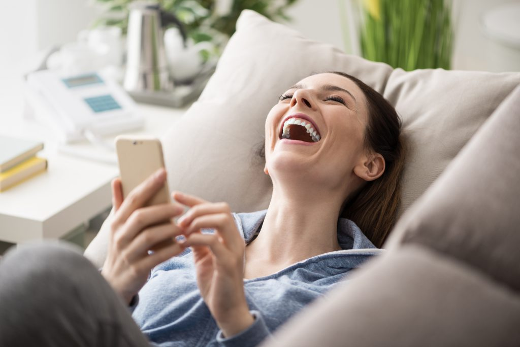 Relaxed smiling woman on the couch at home she is using a smartphone and laughing