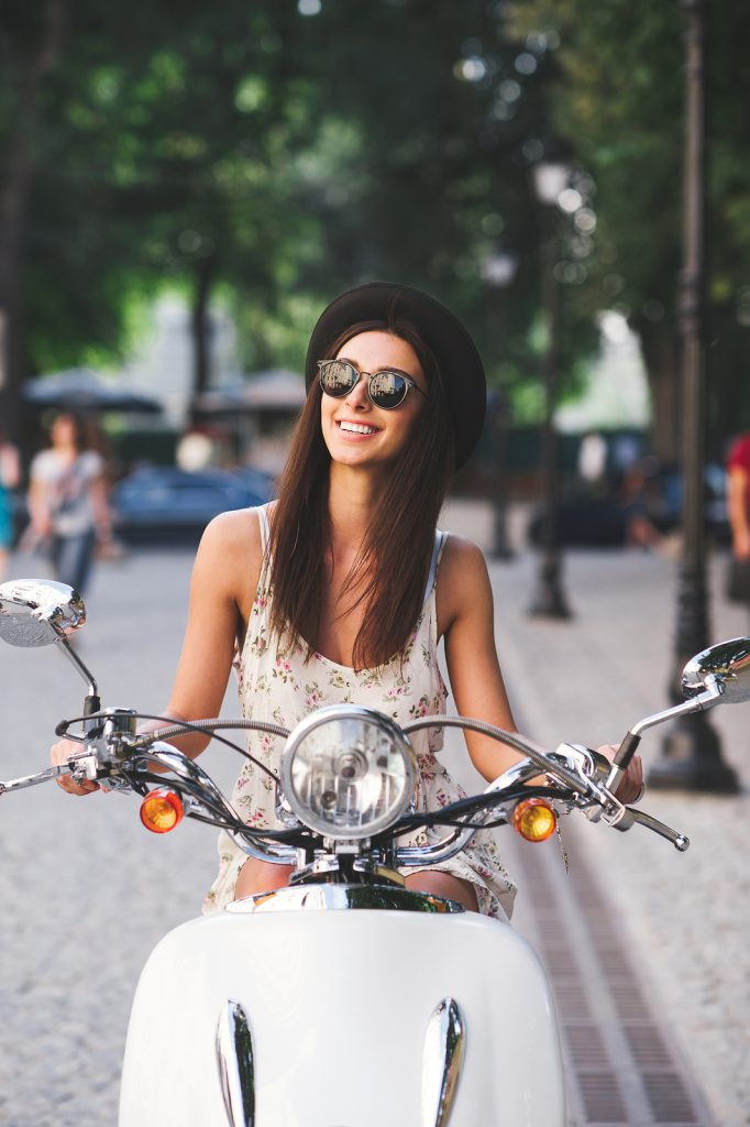 Vertical portrait of young cheerful girl driving scooter in in european city. Stylish beautiful woman in summer clothes on motorbike