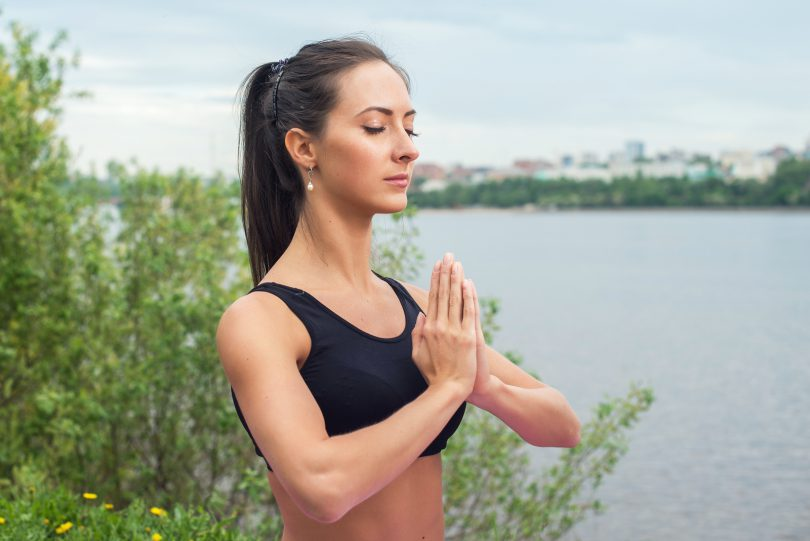 woman in the prayer position meditating in nature